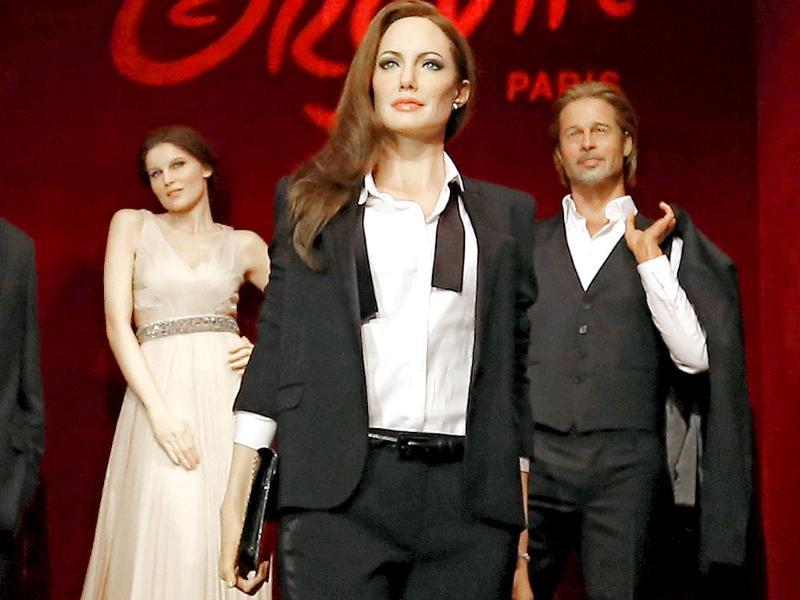 A life-size wax model of US actress Angelina Jolie, centre, French actress Laetitia Casta, left, and US actor Brad Pitt are displayed during a media presentation at the Grevin Museum (AP Photo)
