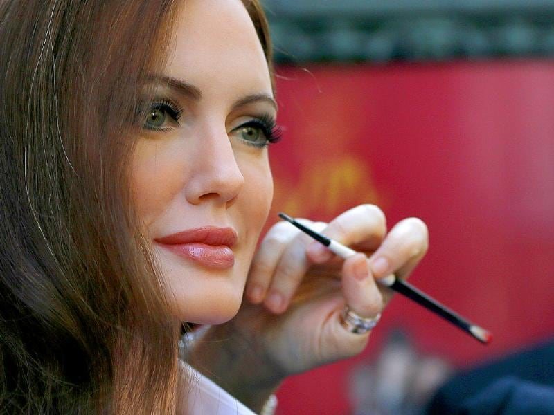 A stylist works on the wax figure of actress Angelina Jolie displayed in front of the Grevin wax museum during a press presentation in Paris (Reuters Photo)