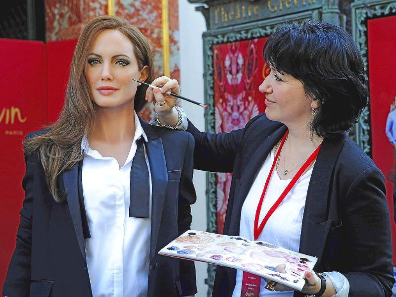 An employee of the Grevin Museum, Berangere Prost, right, applies the final touches to the life-size wax model of US actress Angelina Jolie, in front of the museum, during a media presentation in Paris (AP Photo)