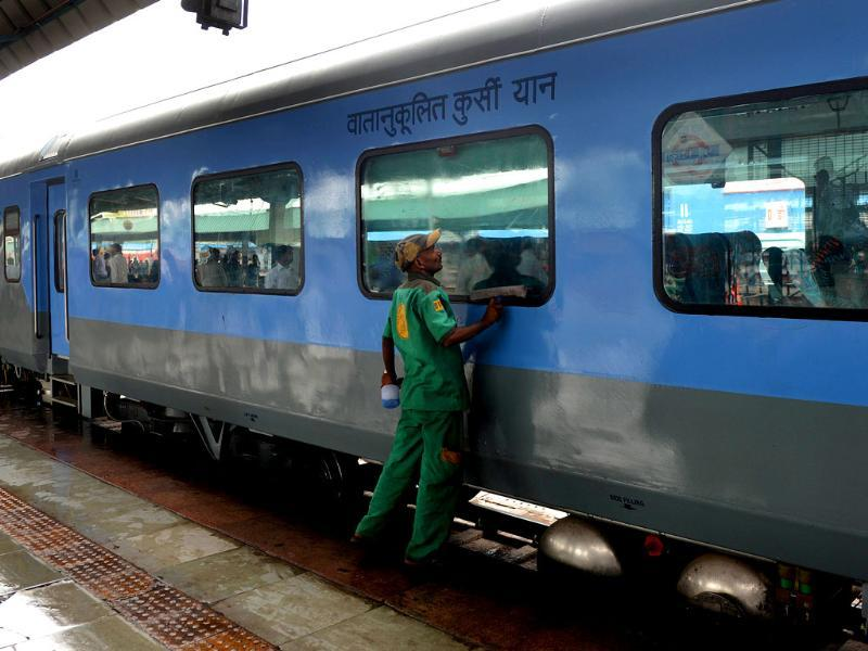 An Indian railways worker cleans a coach prior to the trial run of a high-speed train between New Delhi and Agra is flagged off at New Delhi railway station. (AFP Photo)