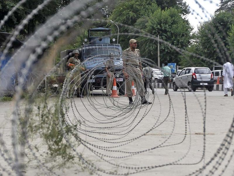 A cop stands guard next to concertina wires during a strike in Srinagar. PM Modi was greeted by near-empty streets lined by security personnel on his first official visit to Kashmir, as separatists enforced a strike. (Reuters photo)