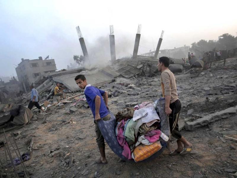 Palestinians try to salvage what they can of their belongings from the rubble of a house destroyed by an overnight Israeli airstrike in Gaza City. (AP Photo)