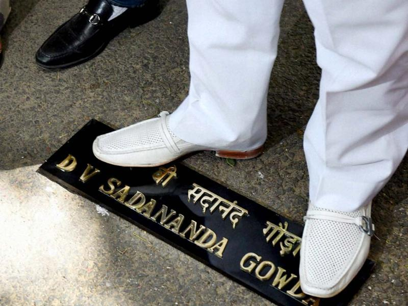Congress ex-MLA Mukesh Sharma stands on the name-plate of railway minister DV Sadananda Gowda during a protest against the Rail Budget, outside Gowda's residence in New Delhi. (PTI Photo)