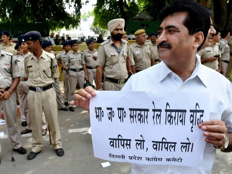 A Congress worker displays a placard during a protest against the Rail Budget outside the residence of railway minister DV Sadananda Gowda in New Delhi. (PTI photo)
