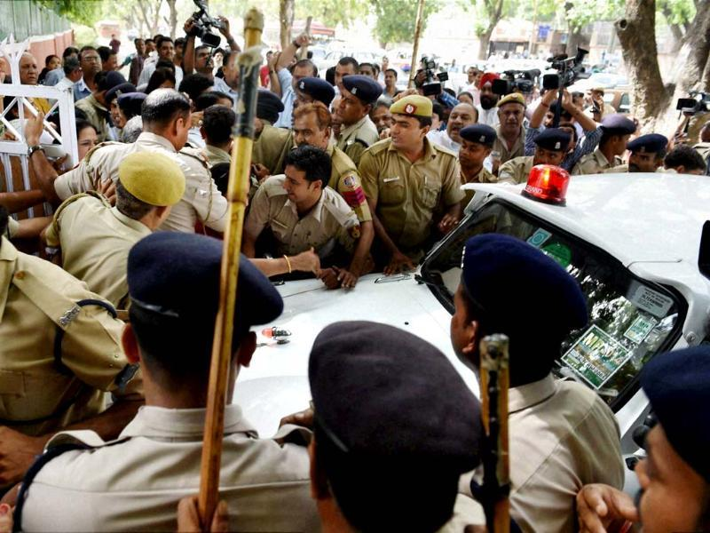 Policemen escort the car of railway minister DV Sadananda Gowda during a protest by Congress workers against the Rail Budget outside his residence in New Delhi. (PTI photo)