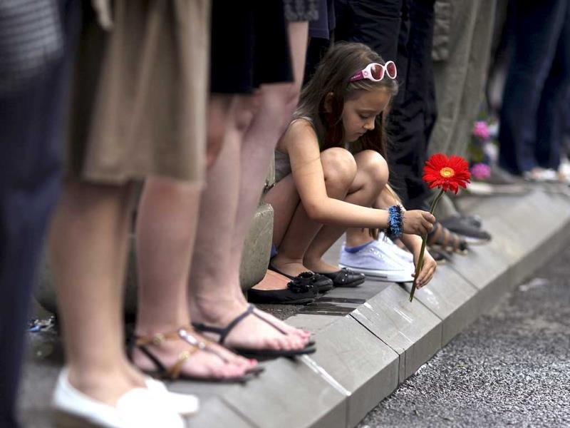 A girl holds a flower crouches by the side of a road, as she waits with others for a truck carrying 173 coffins of newly identified victims of the 1995 Srebrenica massacre, in front of the presidential building in Sarajevo. (Reuters)