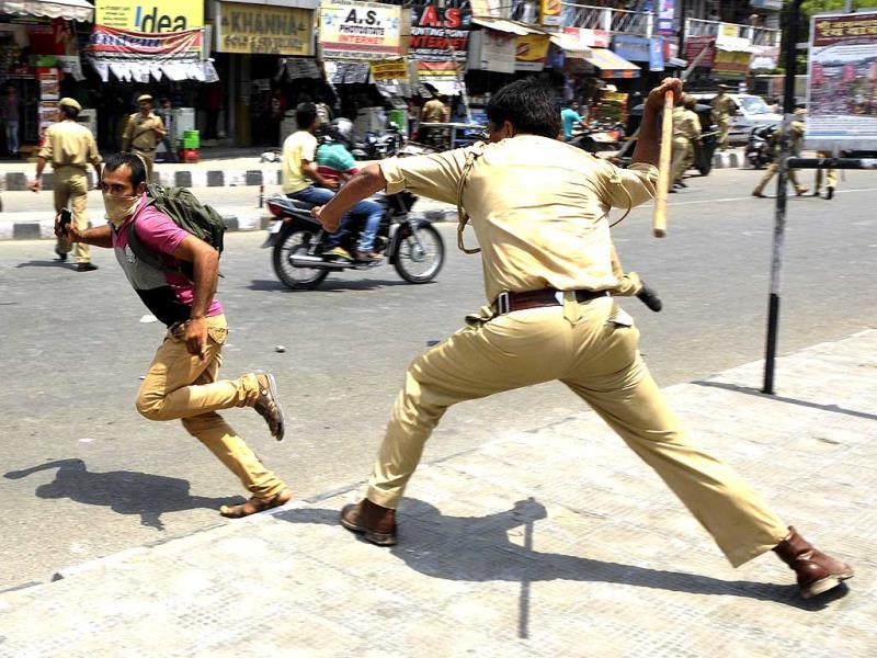 A student tries to escape during a lathicharge by Police perssonals, in Jammu. (Nitin Kanotra/HT Photo)