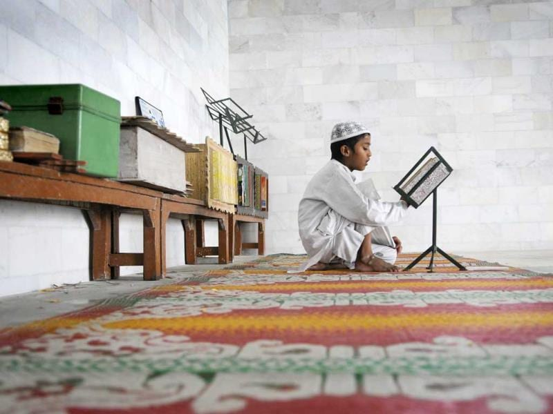 A muslim boy recites verses from Quran on the 10th day of Ramadan, at a Mosque in Noida.(Burhaan Kinu/HT Photo)