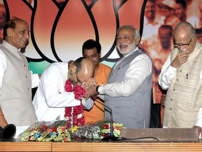 Prime Minister Narendra Modi greets newly appointed Bharatiya Janata party (BJP) president Amit Shah as outgoing party president Rajnath Singh, and BJP senior leader L K Advani looks on, at the party's headquarters in New Delhi. (Ajay Aggarwal/HT Photo)