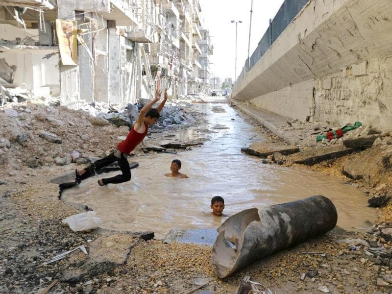 A boy dives into a crater filled with water in Aleppo's al-Shaar district. (Reuters)