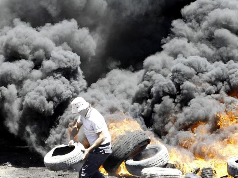 A Palestinian burns tires during clashes with Israeli security forces following a protest in the village of Kfar Qaddum, near the northern city of Nablus, in the occupied West Bank. (AFP Photo)