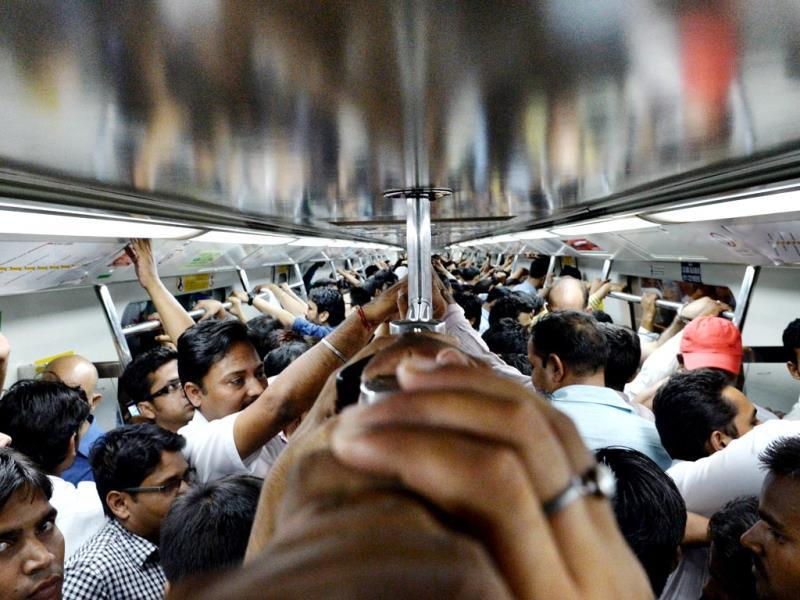 Commuters hold onto the rail inside a carriage of the metro train in New Delhi. (AFP Photo)