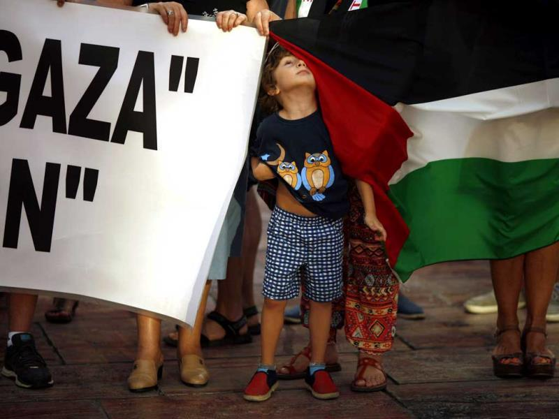 A child looks up while standing in between a Palestinian flag and a banner during a protest to call for an end to the Israeli air strikes on Gaza (Reuters photo)