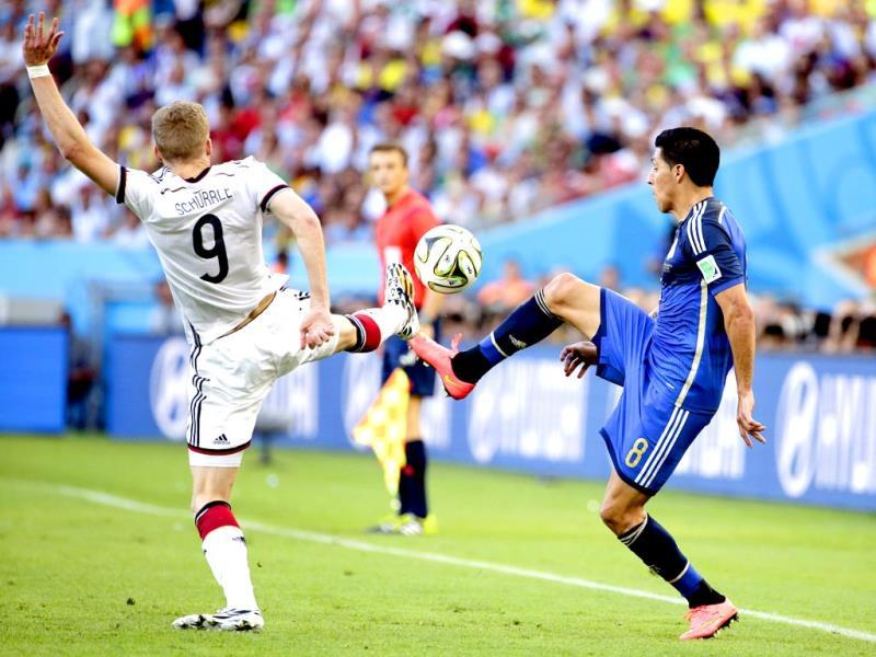 Germany's Andre Schuerrle and Argentina's Enzo Perez clear the ball during the Fifa World Cup final match between Germany and Argentina at the Maracana Stadium in Rio de Janeiro, Brazil. (AP Photo)