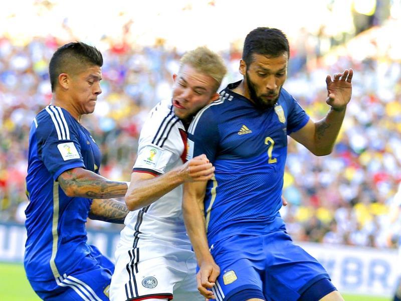 Germany's Christoph Kramer gets hit in the face by Argentina's Ezequiel Garay shoulder (2) while pinned between Garay and Marcos Rojo during the Fifa World Cup final match between Germany and Argentina at the Maracana Stadium in Rio de Janeiro, Brazil. (AP Photo)