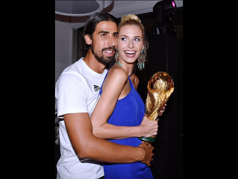 Germany's Sami Khedira and his girlfriend Lena Gercke holding the trophy as they attend the party of the German soccer federation after Germany beat Argentina 1-0 in the soccer World Cup final on July 13, 2014. (AP Photo/DFB, Markus Gilliar)