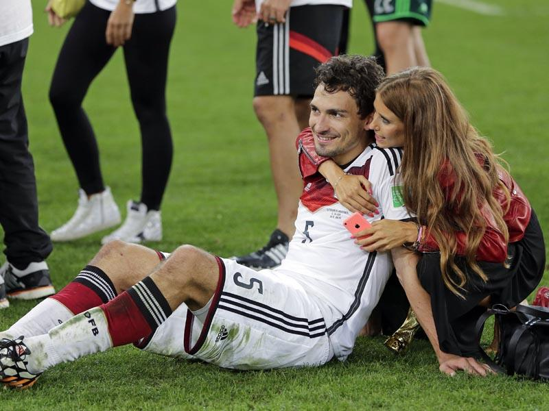 Germany's Mats Hummels is embraced by his partner Cathy Fischer after the World Cup final soccer match between Germany and Argentina at the Maracana Stadium, Brazil on July 13, 2014. (AP Photo/Matthias Schrader)