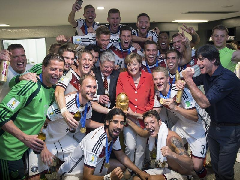German chancellor Angela Merkel, center right, and German president Joachim Gauck, center left, pose with the German soccer squad and the trophy in the changing room, after the Germans won against Argentina by 1-0 in the World Cup soccer final on July 13, 2014. At right, national soccer coach Joachim Loew. (AP Photo-Guido Bergmann, Bundesregierung)