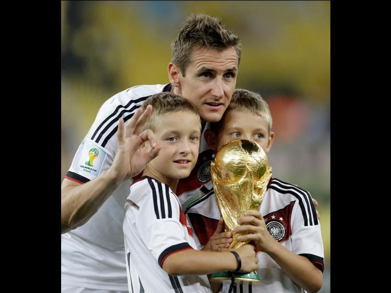 Germany's Miroslav Klose and his sons pose with the World Cup trophy following their 1-0 victory over Argentina after the World Cup final soccer match between Germany and Argentina at the Maracana Stadium in Rio de Janeiro, Brazil on July 13, 2014. (AP Photo/Natacha Pisarenko)