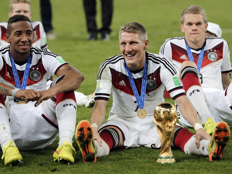 Germany's Jerome Boateng, left, and Bastian Schweinsteiger, center, sit on the pitch with the trophy after the World Cup final between Germany and Argentina on July 13, 2014. Germany won the match 1-0. (AP Photo/Matthias Schrader)