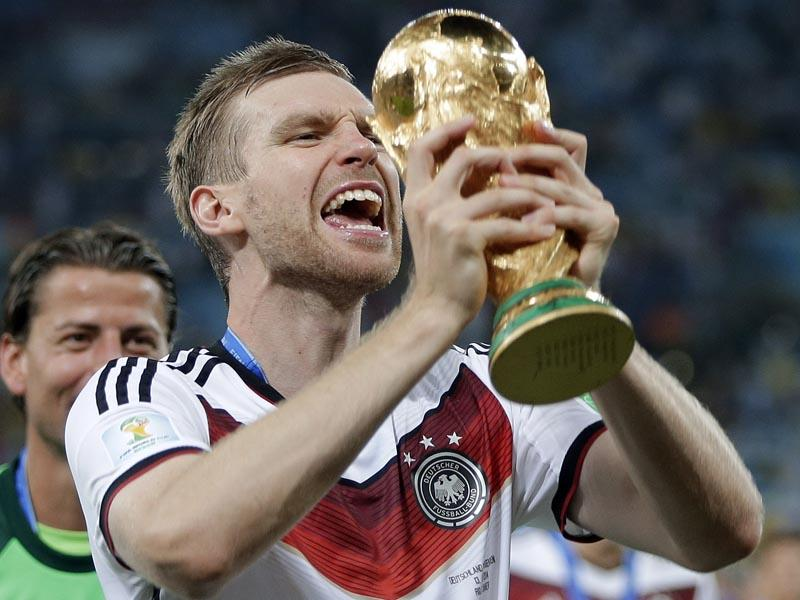 Germany's Per Mertesacker celebrates with the trophy after the World Cup final football match between Germany and Argentina at the Maracana Stadium in Rio de Janeiro, Brazil on July 13, 2014. (AP Photo/Matthias Schrader)