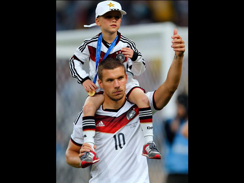 Germany's Lukas Podolski carries his son Louis Gabriel after the World Cup final between Germany and Argentina. Germany beat Argentina 1-0 to win its fourth World Cup title. (AP Photo/Frank Augstein)