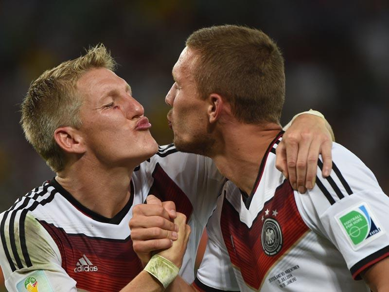 Germany's midfielder Bastian Schweinsteiger (L) and Germany's forward Lukas Podolski celebrate after winning the 2014 FIFA World Cup final football match between Germany and Argentina 1-0 following extra-time on July 13, 2014. (AFP PHOTO/Patrik Stollarz)