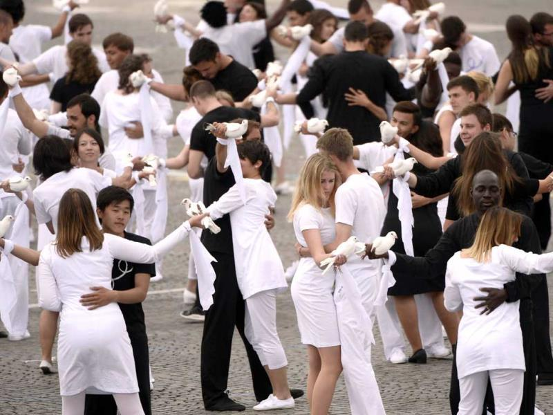 Youths from the 72 invited delegations hold doves as they dance during a performance on the Place de la Concorde in Paris at the end of the annual Bastille Day military parade. (AFP Photo)