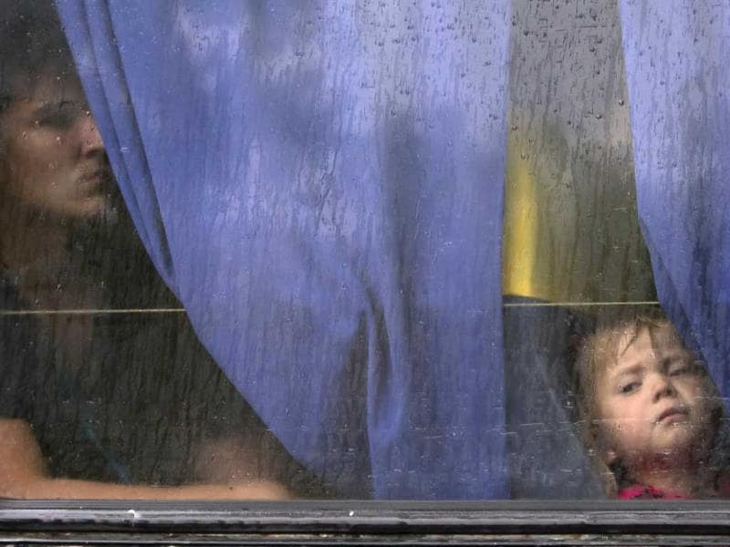 People look through a bus window as they depart as refugees to Russia in the city of Donetsk, eastern Ukraine Monday. (AP Photo)