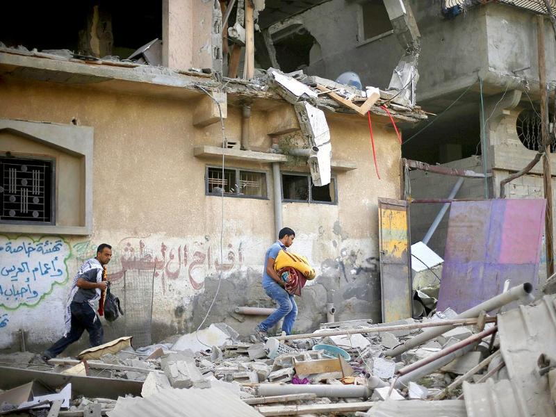 Palestinians carry their belongings as they walk amongst the debris of a house which police said was hit by an Israeli air strike in Gaza City. (Reuters)