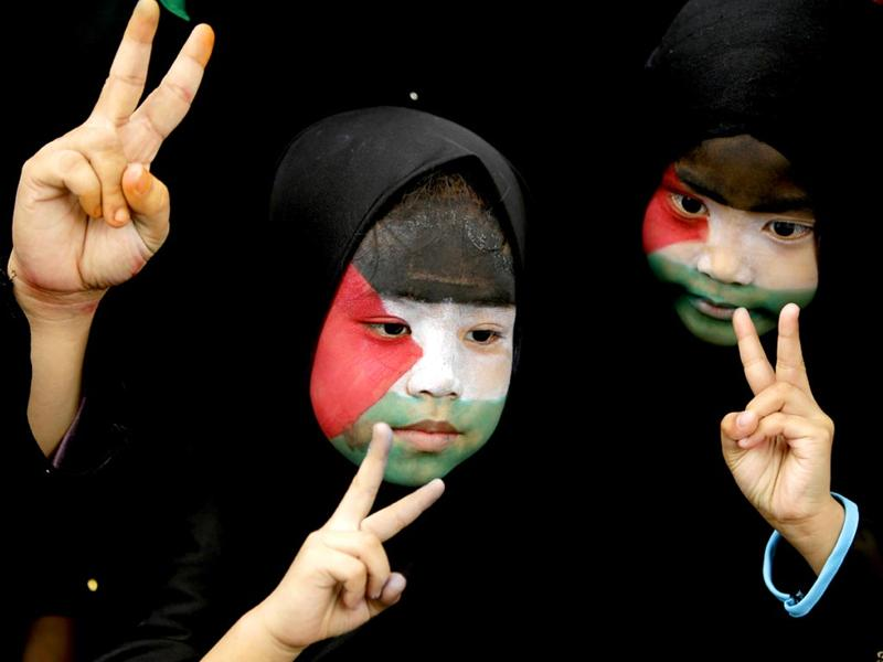 Filipino Muslims, with their faces painted with the colors of the Palestinian flag, flash peace signs during a rally outside Israeli Embassy, Philippines. (AP Photo)