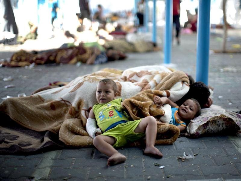 Palestinian children rest at a UN school after evacuating their homes near the border. (AFP Photo)