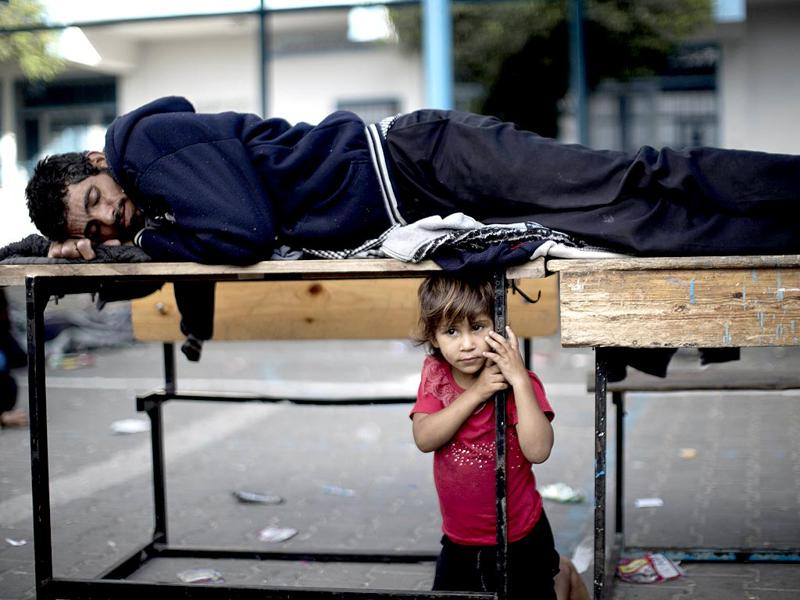 A Palestinian man rests on school desks as families gather at a UN school after evacuating their homes.