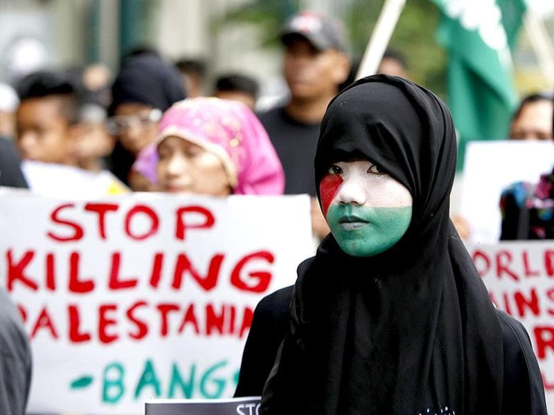 A Filipino Muslim woman, with the Palestinian flag painted on her face, marches towards the Israeli embassy. (Reuters)