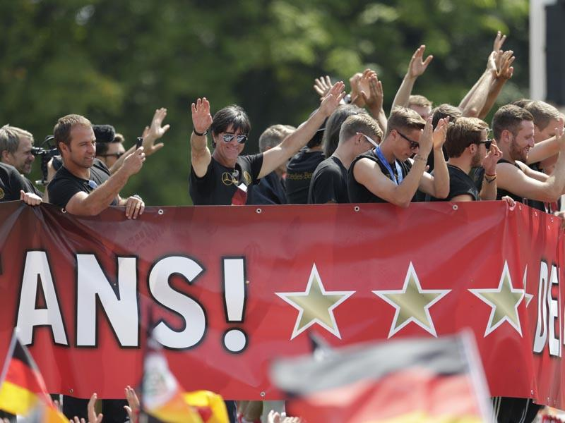 Germany's head coach Joachim Loew waves to the supporters during a fan party after the arrival of the German national soccer team in Berlin on July 15, 2014. Germany beat Argentina 1-0 on Sunday to win its fourth World Cup title. (AP Photo/Petr David Josek)