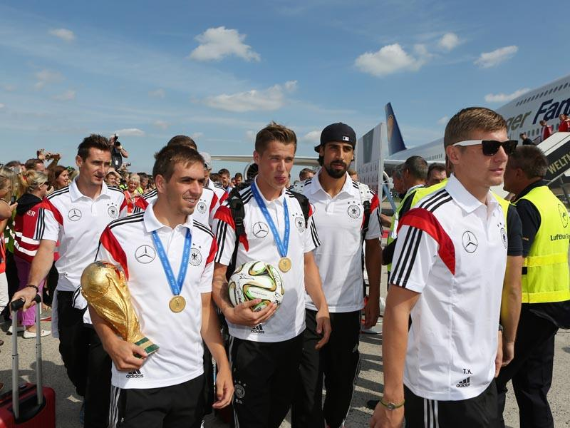 German national soccer players from left : Miroslav Klose, Philipp Lahm, Lars Bender, Sami Khedira and Toni Kroos arrive with the team at Tegel airport in Berlin on July 15, 2014. Germany beat Argentina 1-0 on Sunday to win its fourth World Cup title. (AP Photo/Karina Hessland,pool)