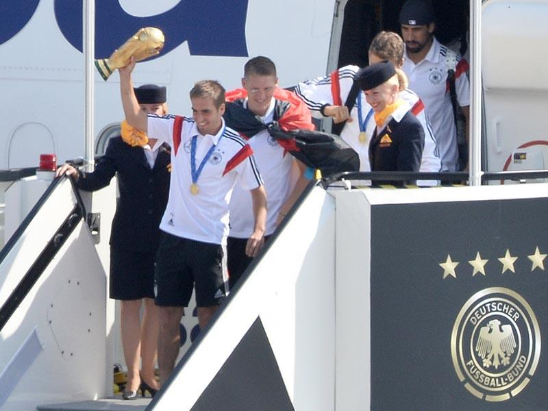 German national football players from left: Philipp Lahm Bastian Schweinsteiger,Thomas Mueller and Sami Khedira, arrive with the trophy at Tegel airport in Berlin on July 15, 2014. The World Cup-winning team has returned home from Brazil to celebrate the country's fourth title with huge crowds of fans. (AP Photo/Bernd von Jutrczenka)