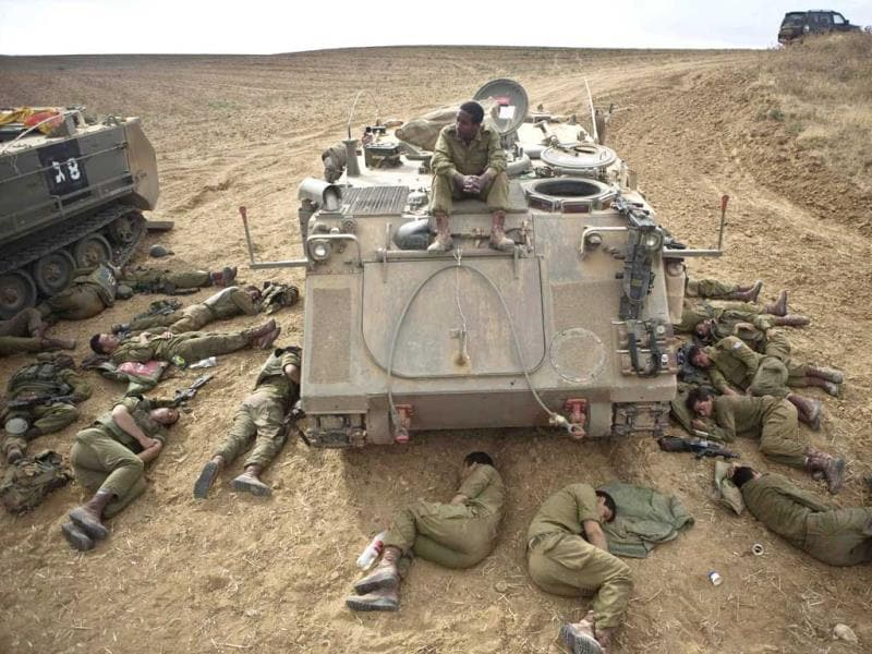 Israeli soldiers sleep on the ground next to an armoured personnel carrier outside the Gaza Strip. (Reuters Photo)