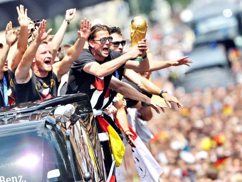 The German football team cheers as they ride in an open-deck bus to Berlin's landmark Brandenburg Gate to celebrate their World Cup title. (AFP Photo)