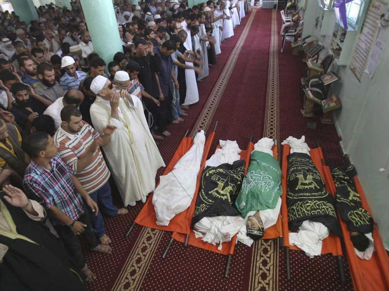 People pray next to the bodies of Palestinians, including three members of Sheik al-Eid family who medics said were killed in an Israeli air strike, during their funeral at a mosque in Rafah in the southern Gaza Strip. (REUTERS)
