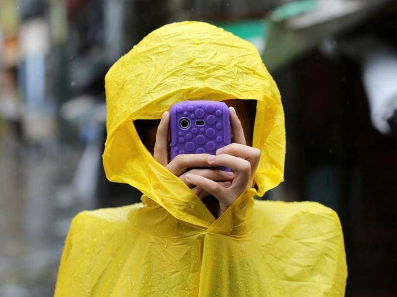 A Filipino resident takes pictures using her smartphone outside a flooded village as Typhoon Rammasun batters suburban Quezon city, north of Manila, Philippines. Typhoon Rammasun knocked out power in many areas but it spared the Philippine capital, Manila, and densely-populated northern provinces from being directly battered when its fierce wind shifted slightly away, officials said. (AP Photo/Aaron Favila)