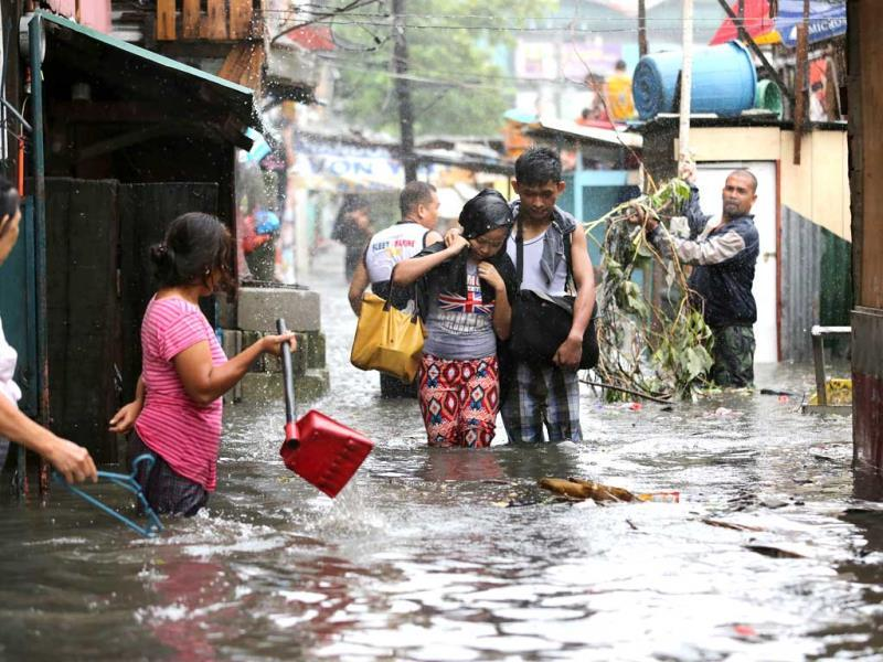 Residents wade through floods as they go back to their home while Typhoon Rammasun batters suburban Quezon city, north of Manila. Philippines. (AP Photo/Aaron Favila)