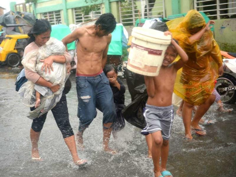 Residents brave strong winds and rain as they evacuate from their homes at an informal settlers' area as Typhoon Rammasun barrels across Manila. (AFP photo)