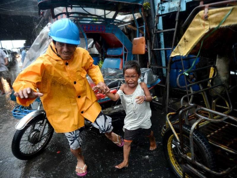A village official leads a child as he is evacuated from their house at an informal settlers' area as Typhoon Rammasun barrels across Manila. (AFP photo)
