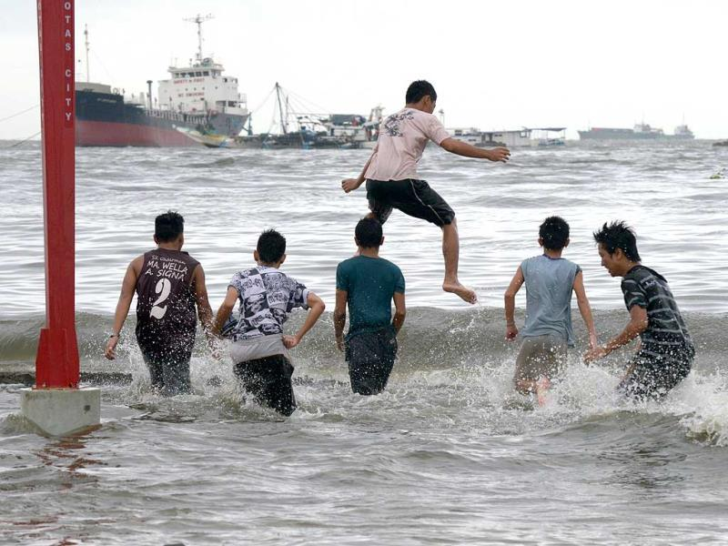 People play near a damaged sea wall as Typhoon Rammasun hit Metro Manila. (AFP photo)
