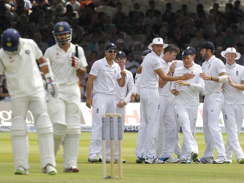 Shikhar Dhawan (2nd L) leaves after losing his wicket for 7 runs as England players celebrate on the first day of the second Test at Lord's Cricket Ground in London. (AFP Photo)