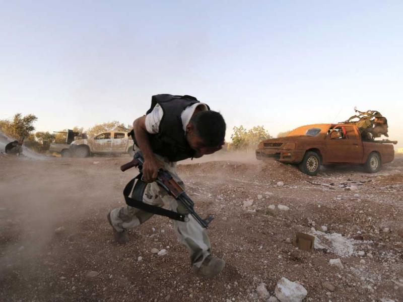 A Free Syrian Army fighter runs while holding a weapon in Wadi Al-Dayf in the southern Idlib countryside. (Reuters Photo)