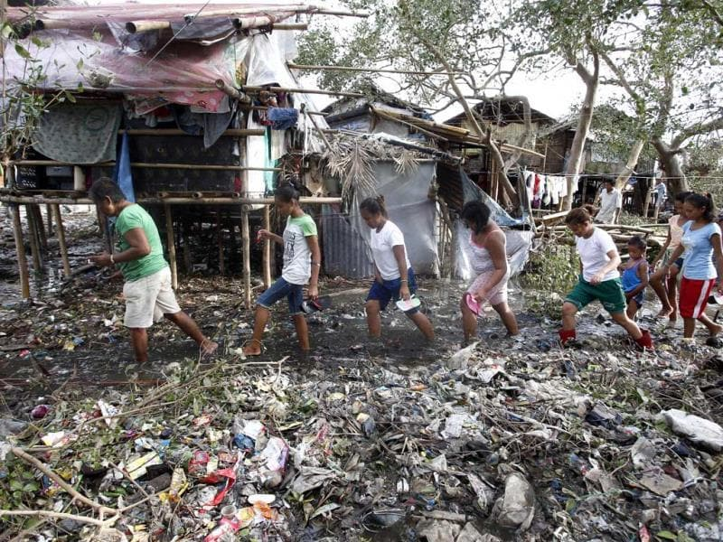 Residents walk amidst debris and mud brought by Typhoon Rammasun (locally named Glenda) in a coastal village of sea gypsies in Batangas city, south of Manila. (Reuters Photo)