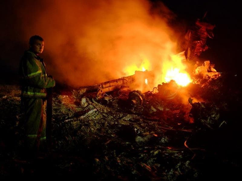 A firefighter stands as flames burst amongst the wreckages of the malaysian airliner carrying 298 people from Amsterdam to Kuala Lumpur after it crashed, near the town of Shaktarsk, in rebel-held east Ukraine, on July 17, 2014. (AFP)