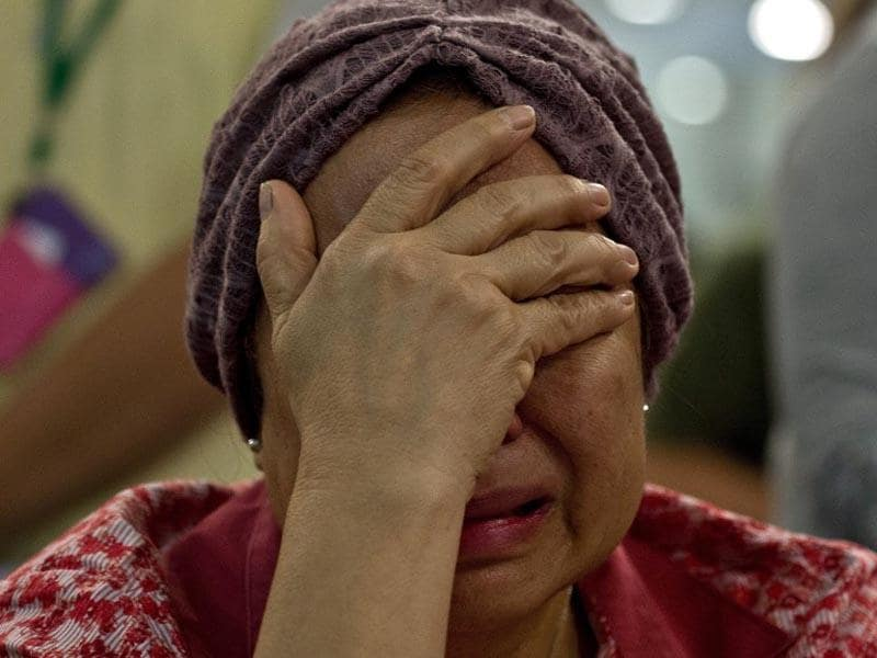 Akmar Binti Mohd Noor, 67, whose sister was onboard Malaysia Airlines flight MH17 from Amsterdam cries outside the family holding area at the Kuala Lumpur International Airport in Sepang on July 18, 2014. (AFP/Manan Vatsyayana)